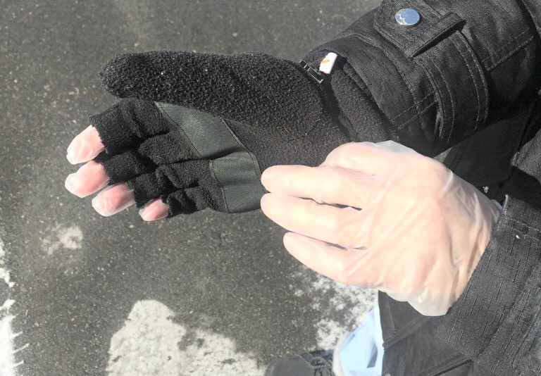 Picture of person wearing vinyl or nitrile glove under fuzzy mittens with removable tips