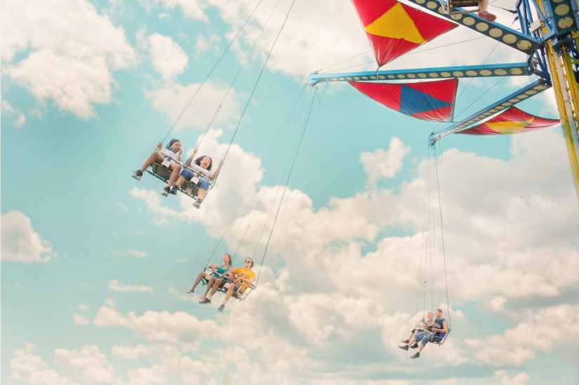 Children enjoying an amusement ride together with a backdrop of a blue sky with fluffy white clouds